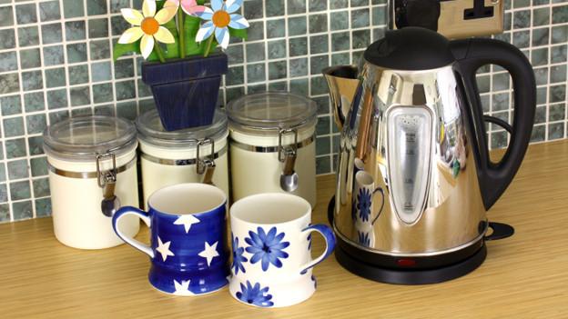 Wasserkocher mit Tassen und Zuckerdosen auf der Ablage einer Küche.