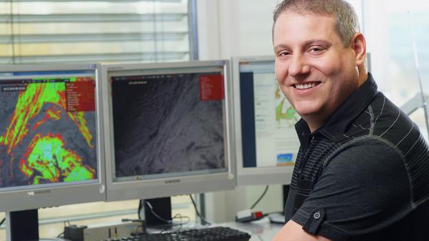 Metereologe sitzt an seinem Arbeitspult vor PCs