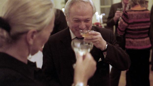 Älteres Paar auf gehobener Party prostet sich mit Champagnergläsern zu.