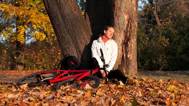 Eine Frau lehnt sich an zwei dicke Baumstämme und gönnt sich eine Pause vom Fahrradfahren.