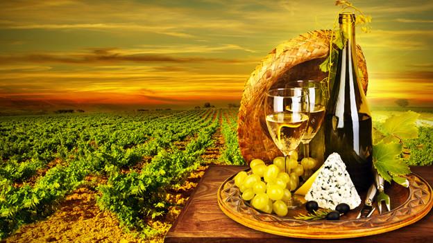 Stillleben mit Weinflasche, Käse und Strohhut in einer ländlichen Gegend.