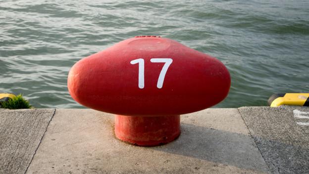 Ein roter Poller mit der weiss aufgedruckter Zahl 17.