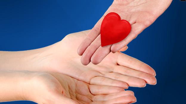 Hand lässt Herz in Hände einer anderen Person gleiten.