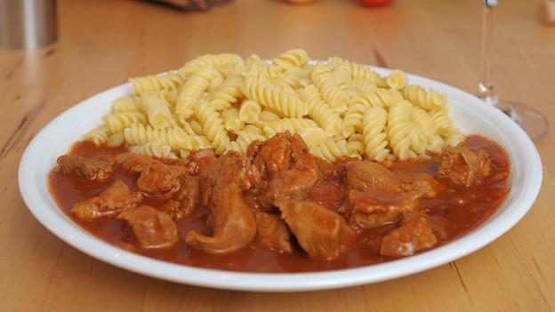 Ein Teller mit Teigwaren sowie Fleischstücken in Bratensauce.