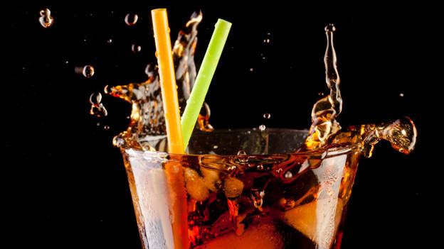 Sprudelndes Getränk in einem Glas mit Eiswürfeln und Strohhalmen.