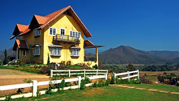 Ein Haus mit knallig gelber Fassade vor tiefblauem Himmel.