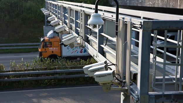Lastwagen fährt unter Brücke hindurch. Daran sind Kameras befestigt, die den passierenden Truck registrieren.