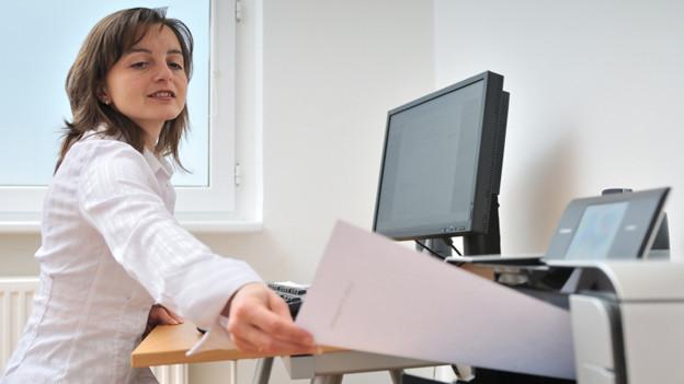 Eine Frau sitzt am Schreibtisch vor dem Computer und greift nach einem Blatt, das vom Drucker ausgespuckt wird.