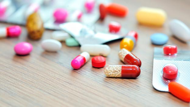 Verschieden grosse und verschieden farbige Pillen ausgestreut auf einem Tisch.