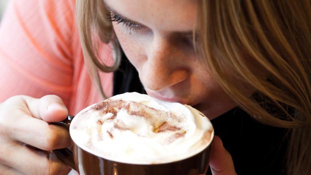 Eine junge Frau trinkt einen Cappuccino.