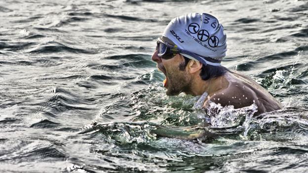 Schwimmer mit Bademütze im Meer.