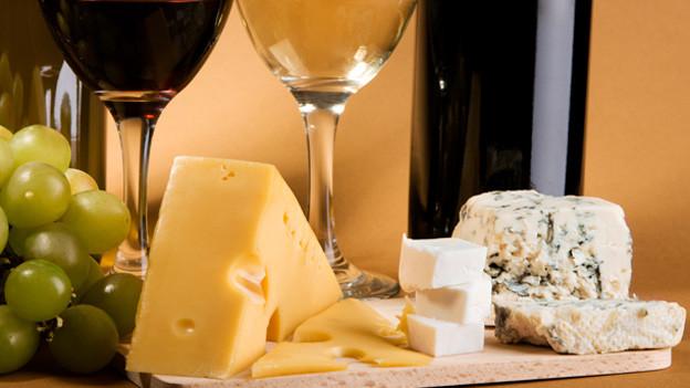 Käseplatte mit Trauben und einem Glas Wein.
