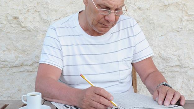 älterer Mann mit Rätselheft.