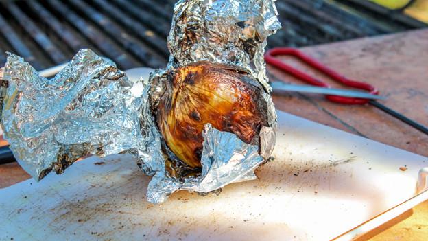 Eine über dem Grill und in Alufolie verpackte Zwiebel nach dem Braten.