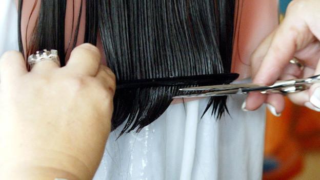 Frisörin schneide einer Kundin die Haarspitzen.