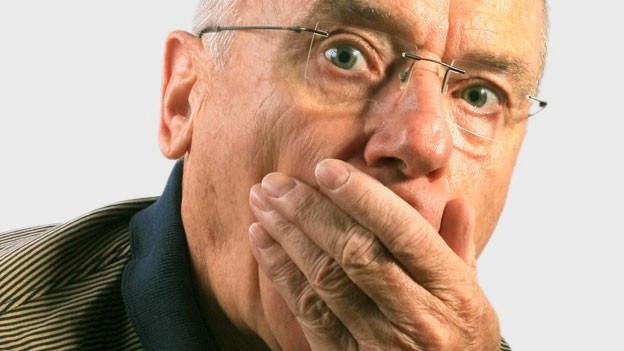 Ein Mann hält sich wegen des Schluckaufs die Hand vor den Mund.