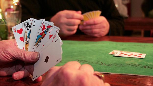 Während eines Jassspiels am grünen Tisch werden die Karten gezählt.