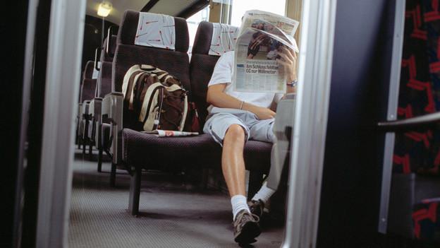 Wanderer in Zugabteil liest Zeitung, auf Stuhl daneben liegt sein Rucksack.