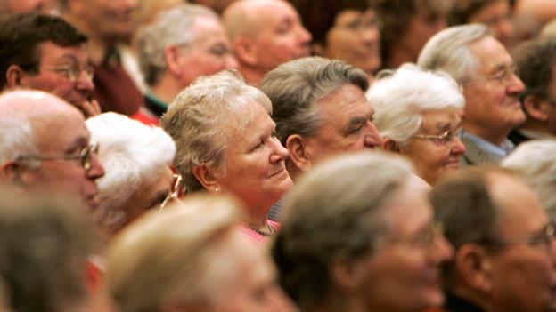Senioren lauschen einer politischen Reede.