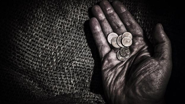 Sehr düstere Aufnahme auf der eine ausgestreckte Hand eines älteren Mannes mit ein paar Geldmünzen zu sehen ist.
