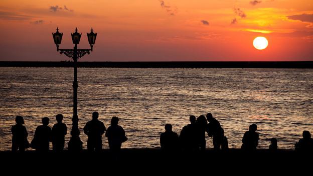 Eine Reihe von Menschen, die vom Ufer aus den Sonnuntergang über dem Meer beobachten.