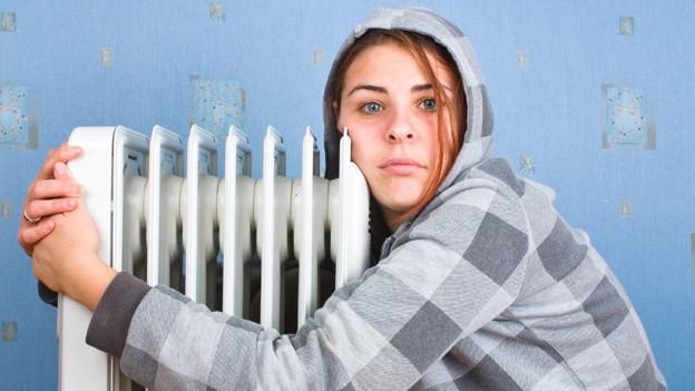 Eine Frau mit Kapuzenjacke umarmt im Wohnzimmer die Heizung.