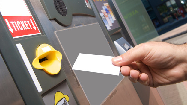 Jemand stempelt sein Parkticket am Automaten in einem Parkhaus ab.