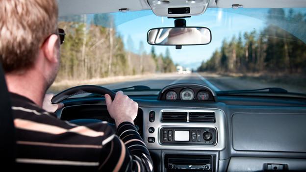 Autofahrer im Cockpit blickt auf Strasse.
