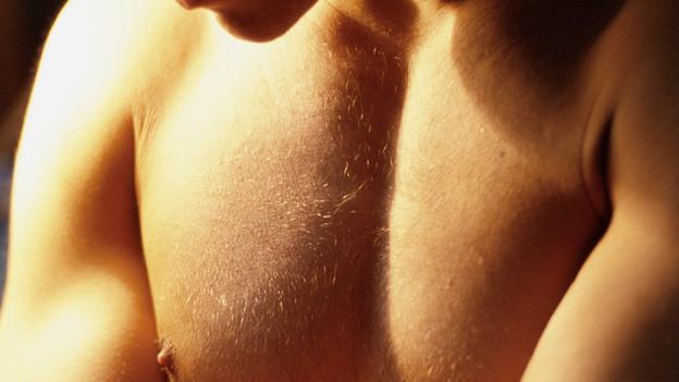 Mann mit nacktem Oberkörper betrachtet seine Brust.