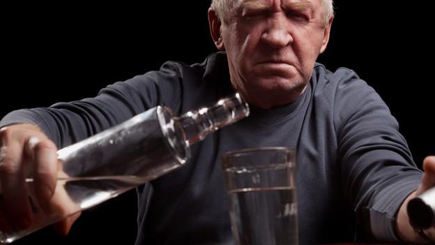 Senior giesst sich ein Glas Schnapps ein.