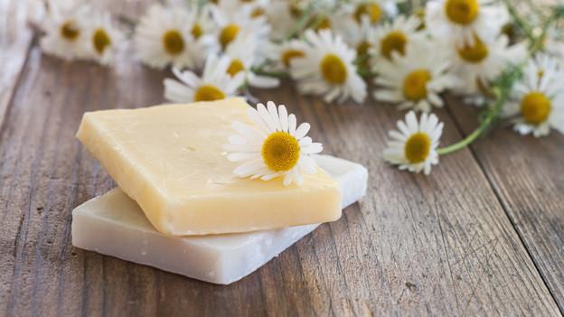 Zwei aufeinanderliegende Stück Seife vor vielen weiss-gelben Margeriten.