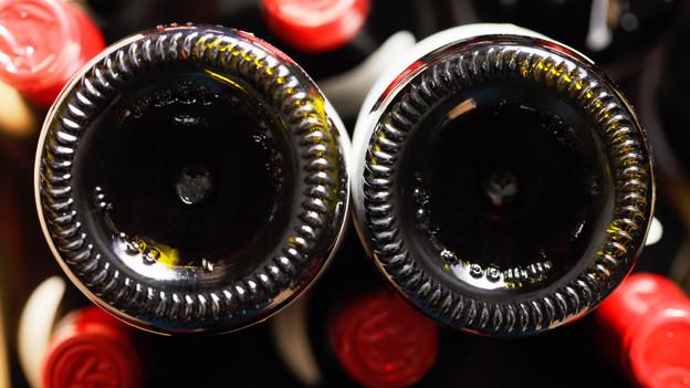 Unterseite zweier Flaschen, die in einer Harasse zwischen weiteren Flaschen stecken.