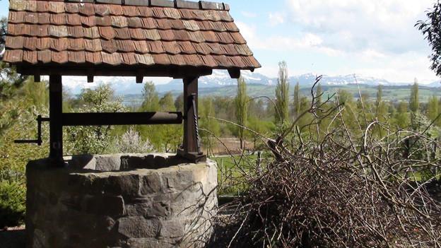 Ein alter Sodbrunnen mit Dach und Kurbel an der ein Kessel hängt, den man bis zum Grundwasser hinablassen kann.