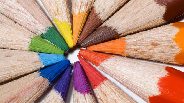 Farbstifte im Kreis mit Spitze in Kreismitte.