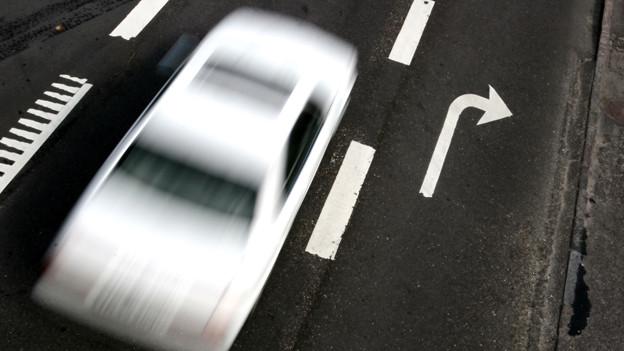 Ein weisses Auto mit Bewegungsunschärfe.