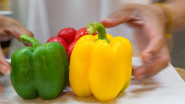 Eine rote, eine grüne und eine gelbe Peperoni, frisch gewaschen auf einer Ablage.