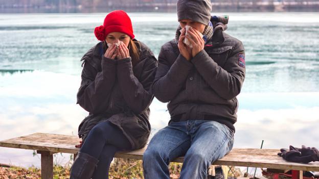 Ein junges Paar sitzt in warmen Kleidern auf einer Bank am See und schneuzt sich die Nasen.