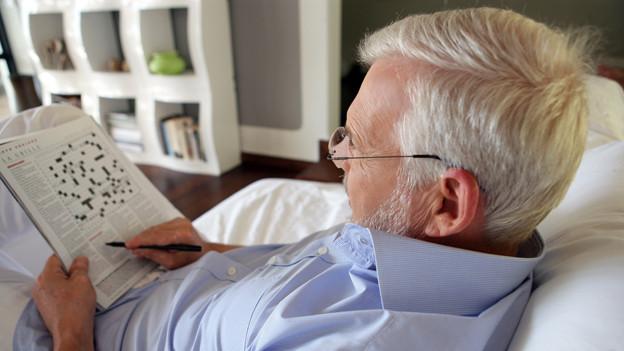 Ein Mann sitzt entspannt im Sofa und löst ein Kreuzworträtsel.