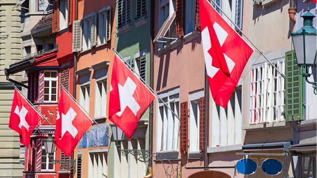 Schweizer Fahnen hängen von Hausfassaden einer alten Stadt.