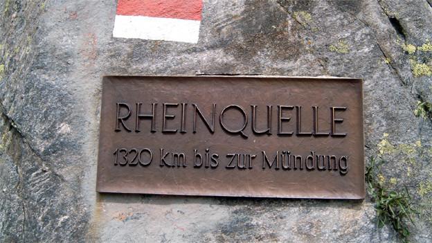 Ein Hinweisschild mit den Worten «Rheinquelle - 1320 km bis zur Mündung», angebracht an einem Felsen.