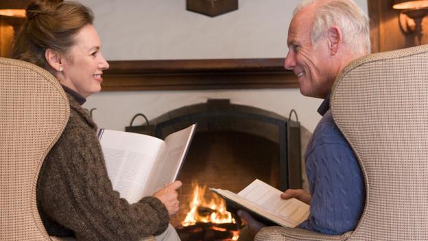 Seniorenpaar sitzt auf gemütlichen Ohrensesseln vor Kaminfeuer und liest jeweils ein Buch.