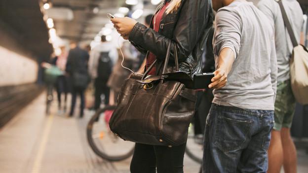 Ein Mann stiehlt einer Frau die Geldbörse aus der Handtasche während sie Musik hörend auf einen Zug wartet.