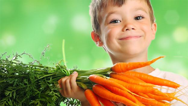 Ein etwa zehjähriger Junge hält lächelnd einen Bund Karotten in der Hand.