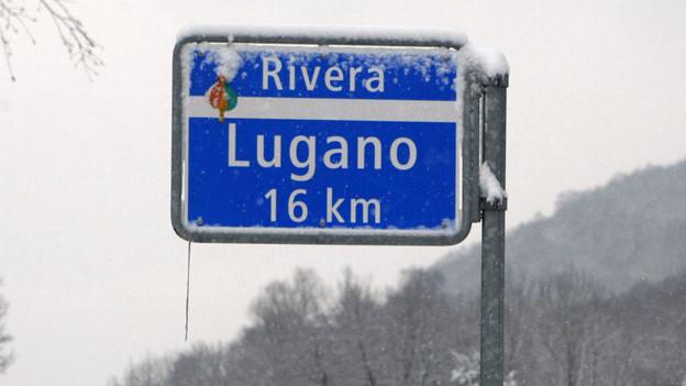 Ein blaues Schild mit weisser Schrift unter einer Schicht Schnee.