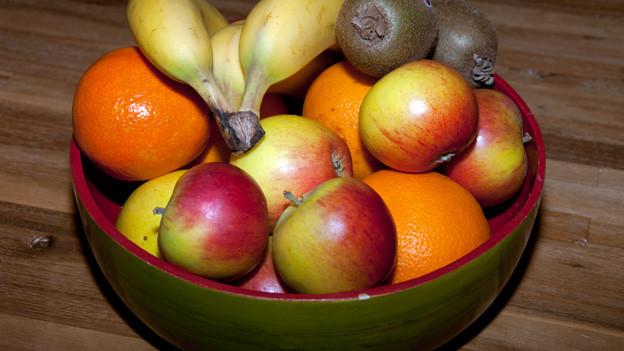 Äpfel, Orangen, Bananen und Kiwi in einer grünen getöpfterten Fruchtschale.