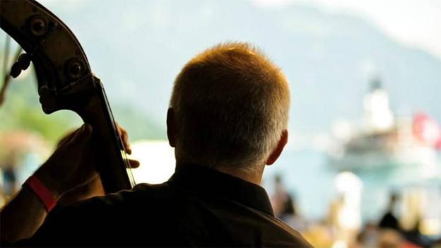 Rückenansicht eines Kontrabass-Spieler, der mit Blick Richtung See spielt.