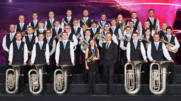 Gruppenfoto mit den Musikerinnen und Musikern vor violettem Hintergrund.