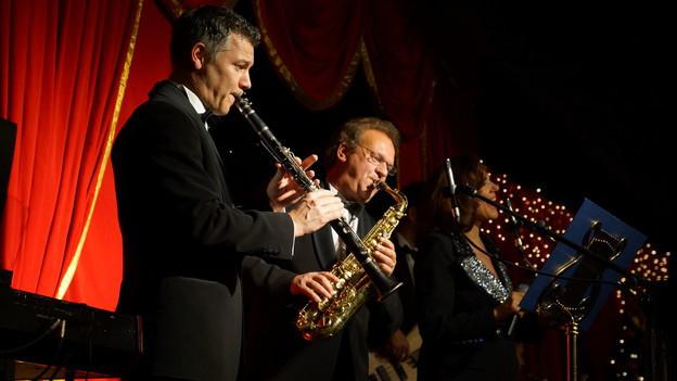 Ein Klarinettist, ein Saxofonist und eine Sängerin auf einer festlich dekorierten Bühne.