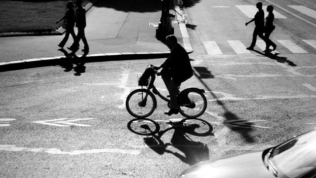 Schwarz-Weiss-Fotografie mit Fussgängern, Fahrradfahrer und Automobilist.