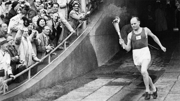 Schwarz-weiss Fotografie mit Paavo Nurvi, der mit der Olympiafackel ins Stadion läuft.